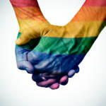gay couple holding rainbow colored hands