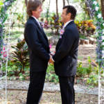 gay couple being married under arch