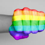 mans fist with rainbow flag overlay