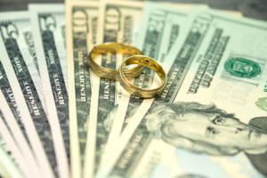 Wedding rings sitting on money