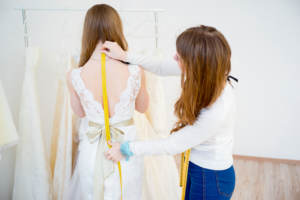 woman having dress measured
