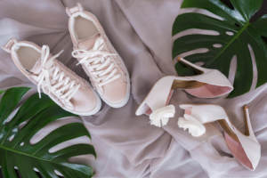 A pair of comfortable sneakers next to some pink high heels