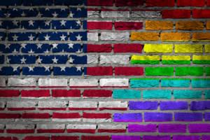 An American flag on a brick wall with LGBTQ stripes