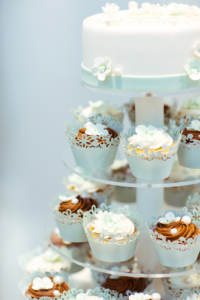 A wedding cake with a variety of cupcakes tiered below it