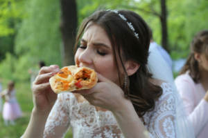 A bride having fun eating food with her hands