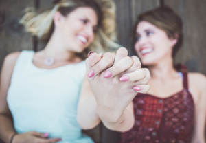 An LGBTQ couple engaged to be married and clasping hands