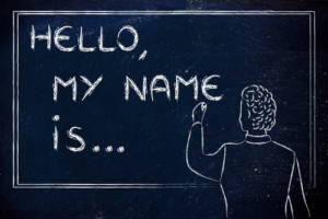 A depiction of a person about to write their name on a chalkboard